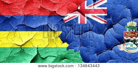 Mauritius flag with Cayman islands flag on a grunge cracked wall