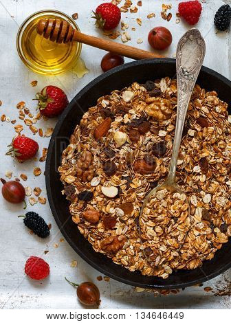 Homemade granola with raisins walnuts almonds and hazelnuts. Muesli and honey . Fresh berries - raspberry strawberry gooseberry mulberry. Healthy Breakfast. Top view