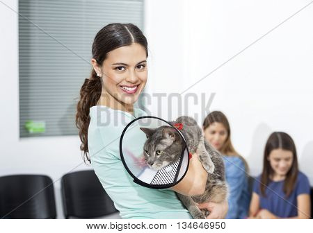 Woman Holding Cat With Cone In Clinic