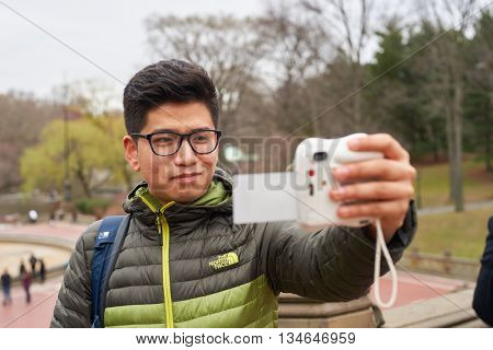 NEW YORK - CIRCA MARCH, 2016: man taking selfie in Central Park. Central Park is an urban park in middle-upper Manhattan, within New York City.