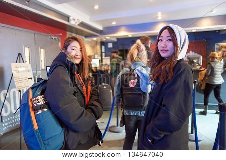NEW YORK - CIRCA MARCH, 2016: indoor portrait of two pretty young women at reception in the hostel. Hostels provide budget-oriented, sociable accommodation where guests can rent a bed
