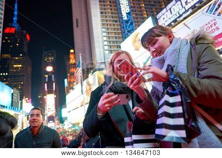 NEW YORK - CIRCA MARCH, 2016: outdoor portrait of young women at Times Square at night time. Times Square is a major commercial intersection and neighborhood in Midtown Manhattan, New York City.