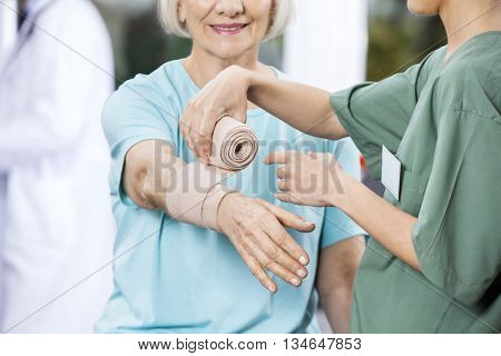 Nurse Putting Crepe Bandage On Patient's Hand At Rehab Center