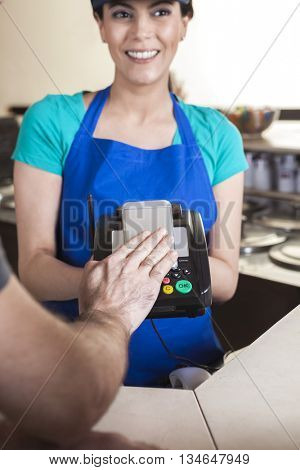 Hand Making NFC Payment On Mobile Phone While Waitress Smiling