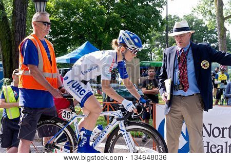 ST. PAUL, MINNESOTA - JUNE 15, 2016: The annual North Star Grand Prix pro cycling event begins with a stage one time trial in St. Paul on June 15 as officials assist a racer at the starting ramp.