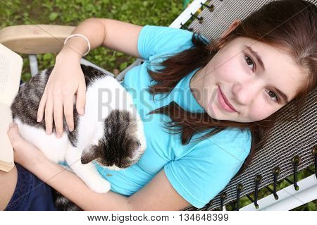 pretty teenage girl in deck chair with book and cat napping on the green summer garden background