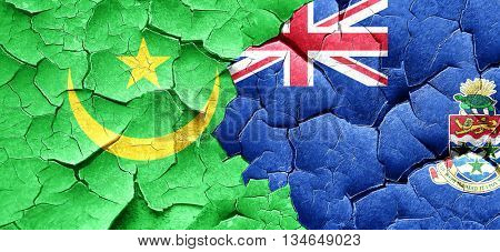 Mauritania flag with Cayman islands flag on a grunge cracked wal