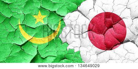 Mauritania flag with Japan flag on a grunge cracked wall