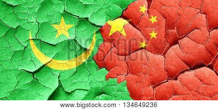 Mauritania flag with China flag on a grunge cracked wall