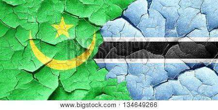 Mauritania flag with Botswana flag on a grunge cracked wall