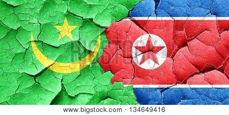 Mauritania flag with North Korea flag on a grunge cracked wall