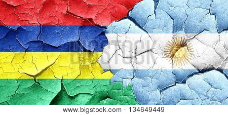 Mauritius flag with Argentine flag on a grunge cracked wall