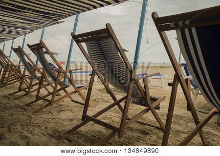 Empty deckchairs on a serene, quiet and clouded beach