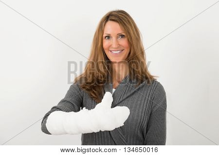 Portrait Of Happy Mature Woman With Broken Hand In Bandage