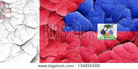 Malta flag with Haiti flag on a grunge cracked wall