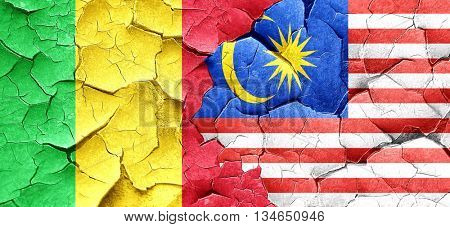 Mali flag with Malaysia flag on a grunge cracked wall