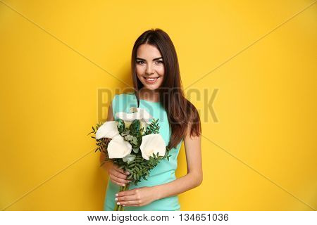 Beautiful young woman holding bouquet on yellow background