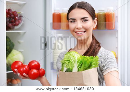 Young woman with purchase box full of vegetables standing beside fridge