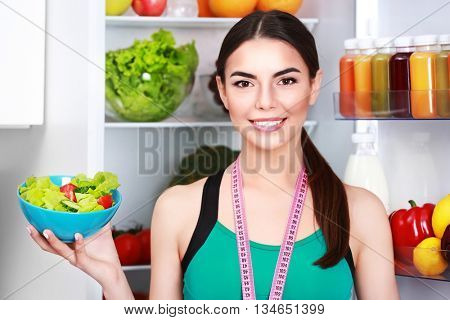 Young woman with tape line on her neck standing beside fridge