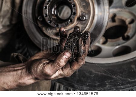 Dirty man hand with gear and car wheel