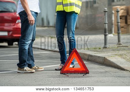 Couple Standing Near Triangular Warning Sign With Broken Down Car