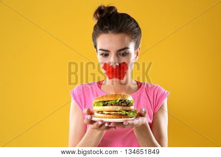 Woman with tied mouth holding hamburger on yellow background