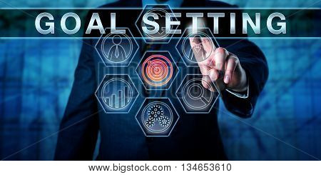 Human resources manager touching GOAL SETTING on an interactive virtual control screen. Business metaphor and personal development concept for a motivational process aimed at improving performance.
