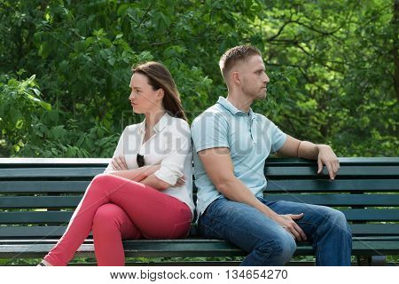 Unhappy Couple Sitting Back To Back On Bench In Park