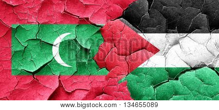 Maldives flag with Palestine flag on a grunge cracked wall