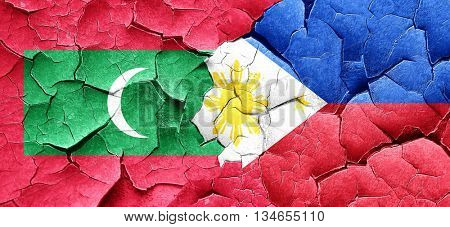 Maldives flag with Philippines flag on a grunge cracked wall