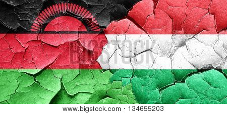 Malawi flag with Hungary flag on a grunge cracked wall