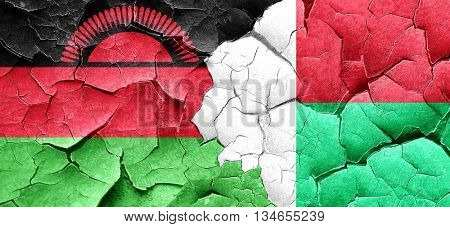 Malawi flag with Madagascar flag on a grunge cracked wall