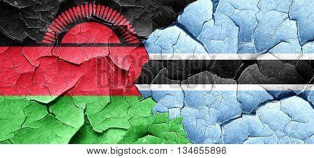 Malawi flag with Botswana flag on a grunge cracked wall