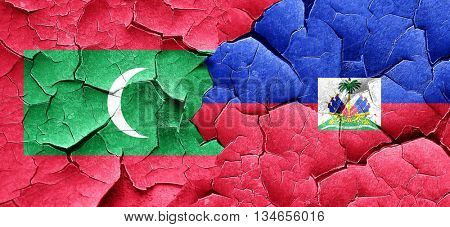 Maldives flag with Haiti flag on a grunge cracked wall
