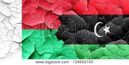 Madagascar flag with Libya flag on a grunge cracked wall