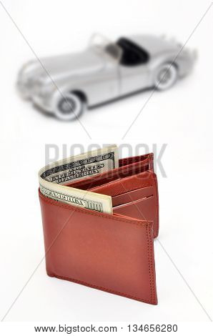 Wallet with Money in US Dollars and blured car background