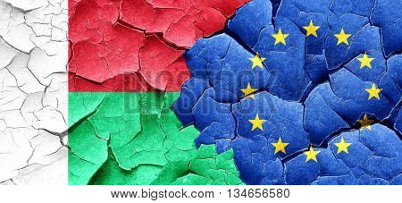 Madagascar flag with european union flag on a grunge cracked wal