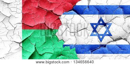 Madagascar flag with Israel flag on a grunge cracked wall