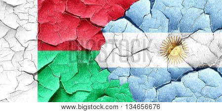 Madagascar flag with Argentine flag on a grunge cracked wall