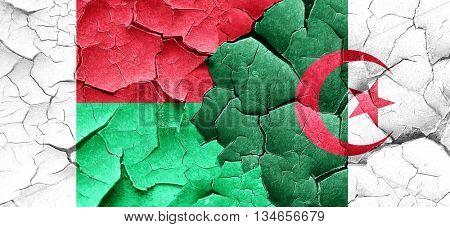 Madagascar flag with Algeria flag on a grunge cracked wall