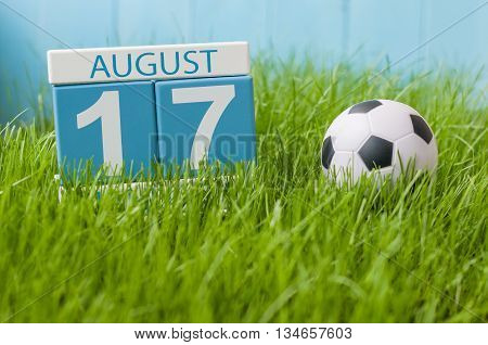 August 17th. Image of august 17 wooden color calendar on green grass lawn background with soccer ball. Summer day. Empty space for text.