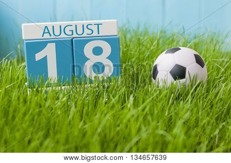 August 18th. Image of august 18 wooden color calendar on green grass lawn background with soccer ball. Summer day. Empty space for text.