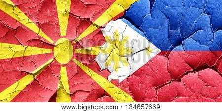 Macedonia flag with Philippines flag on a grunge cracked wall