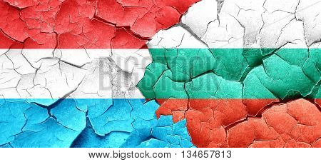 Luxembourg flag with Bulgaria flag on a grunge cracked wall