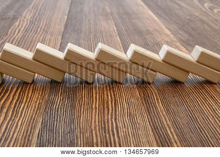 Close-up of wooden bricks lay in a row. Game of physical and mental skill. Removing blocks from a tower. Keeping balance. Full concentration. Entertainment activity. Education and development.
