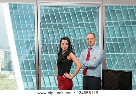 Business team standing in office against the backdrop of a skyscraper