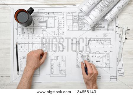 Close-up hands of man holding an engineering divider over drawing plan in top view. Workplace. Engineering work. Construction and architecture. Architect drawing. Measurement. Draftsmanship.