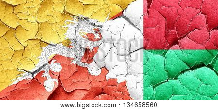Bhutan flag with Madagascar flag on a grunge cracked wall