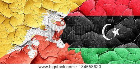 Bhutan flag with Libya flag on a grunge cracked wall