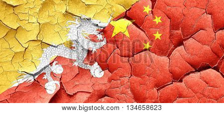 Bhutan flag with China flag on a grunge cracked wall